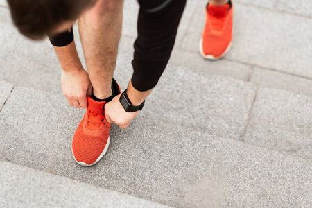 Closeup Of Unrecognizable Young Man Tying Sports Shoe, Running Outdoors On Stairs, High Angle View 免版税图像