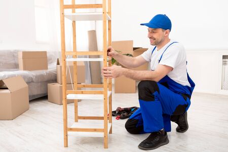 Furniture Assembly Service. Repairman Installing Wooden Shelf Unpacking After Renovation, Wearing Blue Coverall Working In Room Indoor