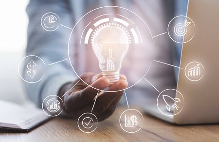 Collaboration, management, business innovation concept. Unrecognizable black businessman holding illuminated light bulb with business process icons in hand while sitting at workplace in office Banque d'images