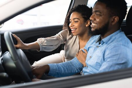 Cheerful Black Couple Testing Car During Test-Drive Buying Auto In Dealership Center. Selective Focus