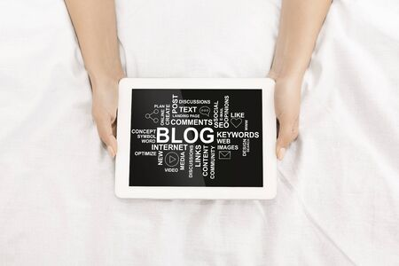 Overhead view of female hands holding tablet with blogging notions on screen, collage