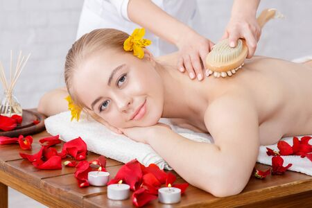 Massage with brush. Smiling beautiful girl receives massage on massage table with rose petals and burning candles
