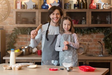 Baking Day. Happy young father and his little daughter posing in kitchen with rolling pin and whisk in hands