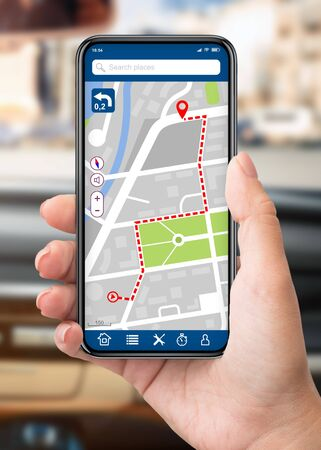 Closeup of female driver using cell phone with gps navigation app on the screen, woman sitting in car Banco de Imagens
