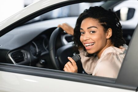 New Car Concept. Joyful Black Lady Buyer Showing Auto Key Sitting In Drivers Seat In Automobile In Dealership. Selective Focus