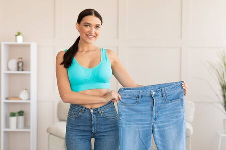 Slimming. Woman Comparing Jeans After Weight Loss Standing At Home, Smiling To Camera.