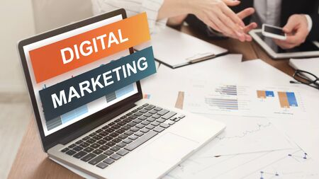 Digital Marketing written on laptop screen, photo of two colleagues working in blurred background