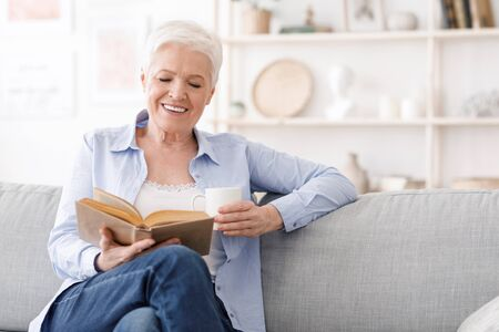 Retirement time. Smiling elderly lady sitting on couch with book and drinking coffee, relaxing at home, free space Stock fotó