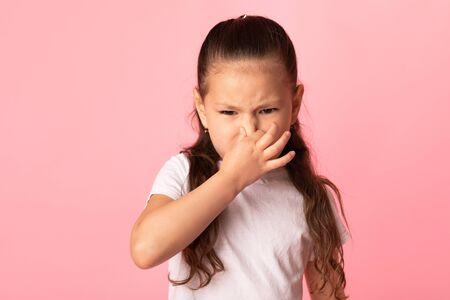 Disgusting Smell. Beautiful asian girl smelling something stinky and intolerable, holding breath with fingers on nose