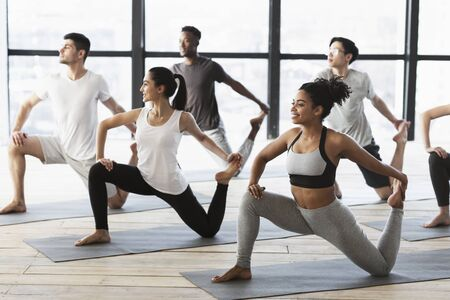 Yoga practice. Group of interracial young people doing Mermaid pose, stretching feet, working out in modern studio