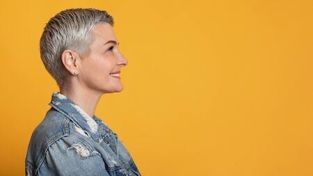 Profile Portrait Of Smiling Beautiful Middle Aged Woman Looking At Copy Space On Yellow Background, Panorama Stock fotó