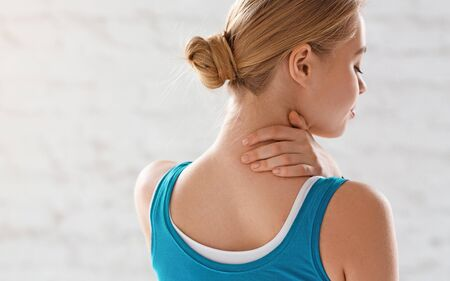 Sports injury concept. Athletic girl feeling pain in her neck against white background, copy space