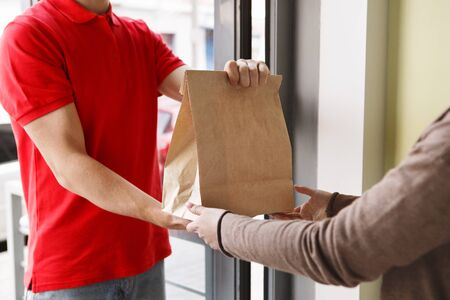 Modern delivery of any order. Girl takes paper package from hands of courier at front door