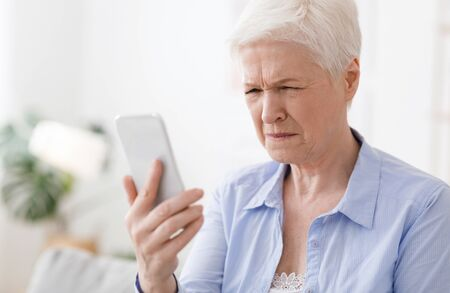 Myopia Concept. Elderly woman squinting while looking at smartphone screen, trying to read message, closeup Stockfoto