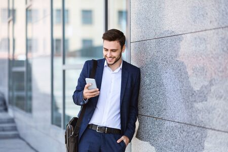 Confident millennial enterpreneur checking messages on his mobile phone near office building wall in city Stock fotó