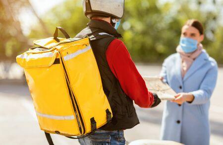 Szybka dostawa. Kurier dostarczający paczkę żywności do kobiety noszącej maskę medyczną stojącą na zewnątrz w mieście. Przycięte, selektywne ustawianie ostrości