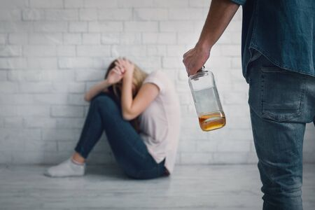 Help for victim of aggressive alcoholic. Wife closes herself from blows of husband, with bottle in hand and sits on floor on white brick wall Stock Photo