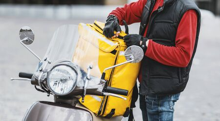 Unrecognizable Courier With Delivery Bag On Scooter Delivering Restaurant Food Standing On City Street Outside. Cropped