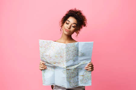Planning Vacation. Pensive African Traveler Girl Holding Tourist Map Choosing Travel Destination Over Pink Background In Studio