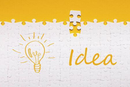 Bonne idée. Dernier détail pour puzzle blanc assemblé avec inscription et lampe allumée sur fond jaune Banque d'images