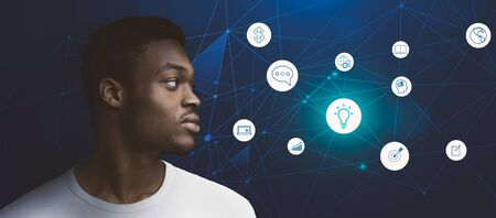 Male profile and digital symbols. Half-turned close up portrait of confident african american man looking at abstract icons, panorama Banque d'images