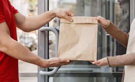 Transfer of parcel on doorstep of house. Courier and girl hold paper package, side view, close up Standard-Bild