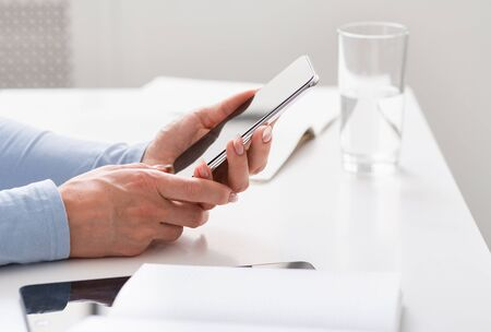 Modern work with mobile devices. Women hands are holding smartphone on table is tablet, pad and glass of water