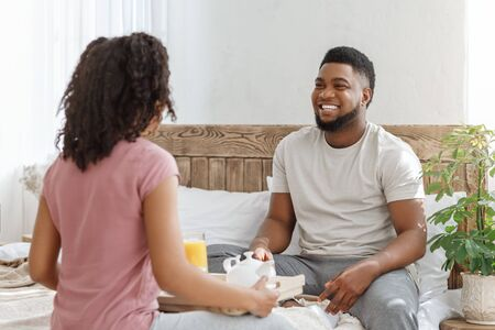 Cheerful black man looking at his girlfriend brought breakfast in bed