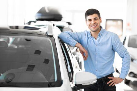 Concepto de propiedad. Guapo apoyado en su coche nuevo de pie en el centro de distribución, espacio libre