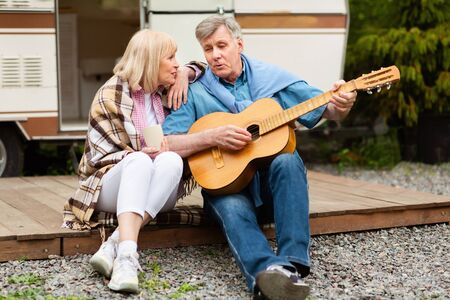 Retired couple with acoustic guitar singing together near their motorhome at campsite Stock fotó