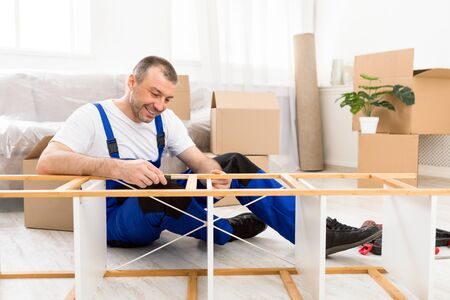 Happy Furniture Assembler In Blue Coverall Fixing Shelf With Screwdriver Providing Assembling And Transportation Services Working Indoor