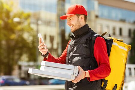 Delivery Service. Courier Guy With Pizza Boxes Using Cellphone Delivering Restaurant Meal Walking In City.