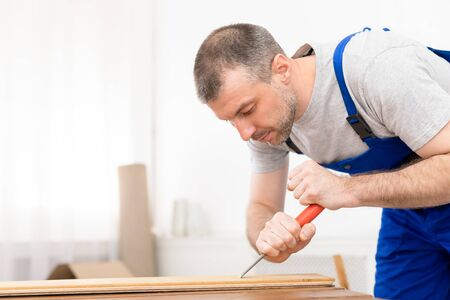 Carpenter Making Furniture Working With Wooden Board Indoor, Wearing Blue Coverall. Selective Focus, Empty Space Standard-Bild