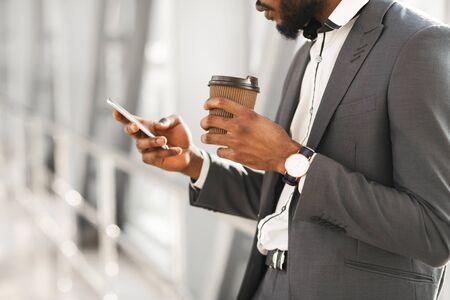 En attente de vol. Homme d'affaires noir méconnaissable utilisant un smartphone prenant un café debout à l'intérieur de l'aéroport. Mise au point sélective et recadrée