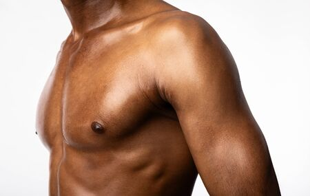 Building Chest Muscles. Unrecognizable Muscular African Man Posing Over White Background. Studio Shot, Cropped