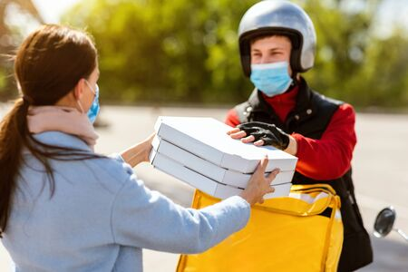 Pizza Delivery Concept. Courier Boy Giving Pizzeria Boxes To Customer, Wearing Protective Mask Standing On Street Outdoors. Selective Focus