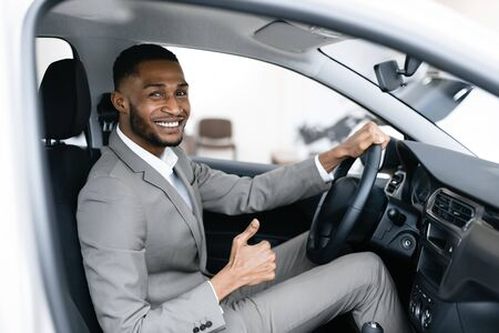 Great Car. African Businessman Gesturing Thumbs Up Sitting In Drivers Seat In Auto Dealership Shop. Selective Focus