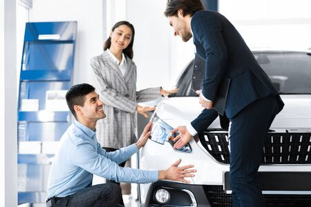 Special Offer. Car vendor showing brand-new vehicle to young couple, spouses examining auto
