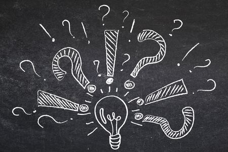 Problem solving. Questions, exclamation marks around lamp drawn in chalk on blackboard