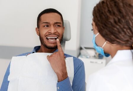 Black guy in pain visiting dentist, showing female doctor painful teeth