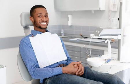 Happy black guy sitting on dentist chair and smiling at camera, attending dental clinic, copy space
