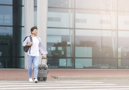 Handsome young man walking with luggage out of airport, carrying suitcase and crossing road to shuttle bus station, copy space Reklamní fotografie
