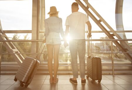 Romantic Travel. Loving couple planning honeymoon, looking at window in airport, copy space, flare sun light, back view