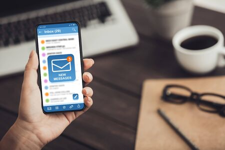 Email Marketing. Unrecognizable Woman Holding Smartphone With New Mail Notification Icon On Screen, Sitting At Desk In Office