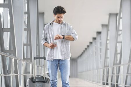 No Time For Transfer. Worry Man Looking At Wristwatch In Airport, Late For His Flight, Standing In Terminal Corridor With Luggage And Smartphone