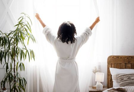 Perfect Morning. Unrecognizable woman dressed in white bathrobe opening window curtains at home, enjoying start of the day, rear view