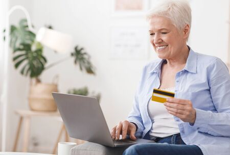 Purchase Online. Positive Elderly Woman Shopping In Internet With Laptop And Credit Card, Sitting On Sofa At Home, Closeup