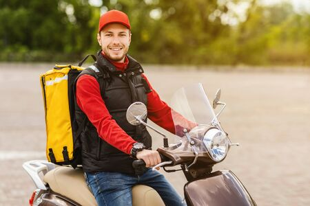 Cheerful Courier Sitting On Scooter Delivering Food In Yellow Backpack Bag, Posing Smiling To Camera Outdoors. Empty Space Stock fotó