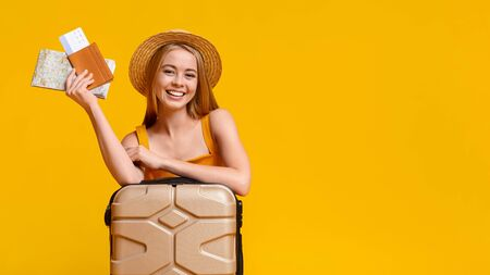 Happy girl tourist lean on suitcase and holding flight tickets and map, ready to travel, posing over yellow background with copy space