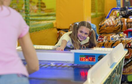 Family leisure. Cheerful girl playing air hockey game with her mum at kids amusement center